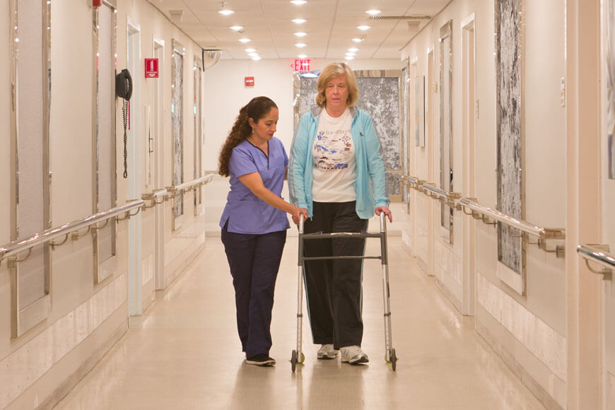 Nurse helping patient with mobility issues at our Long Island hospital